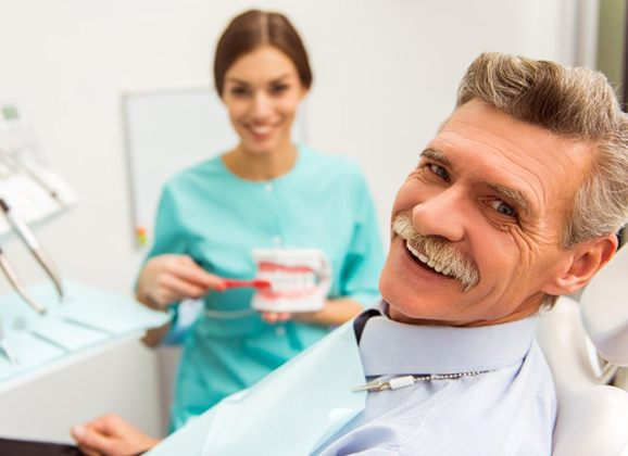 older man in dental chair learning about dentures in Brooklyn