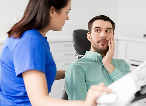 Man in dental chair for emergency dentistry treatment