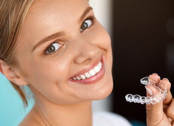 Woman holding an Invisalign tray