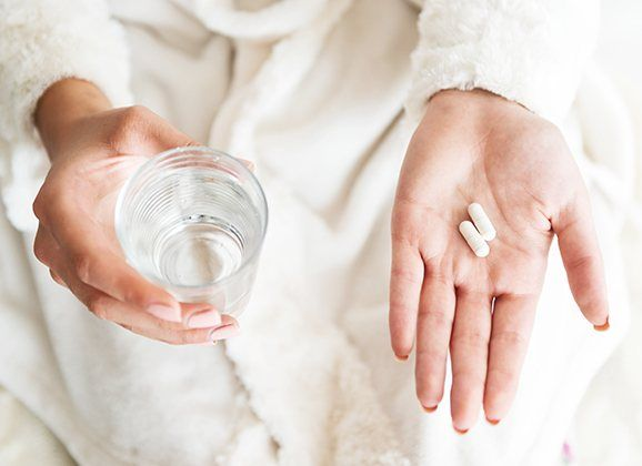 Patient holding glass of water and antibiotic pill