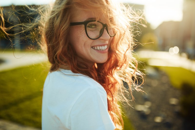 Closeup of woman with red hair smiling outside